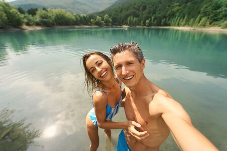 happy couple travelers making selfie on beautiful mountain lake background. POV closeup. outdoor adventure, wanderlust and travel concept. Imagens