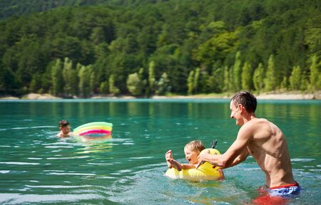 Athletic happy man having fun with kids in mountain lake with clear blue water. Family swimming, hot summer bathing, enjoing vacation outdoors. Family outdoor adventure, beautiful scenery Stock Photo