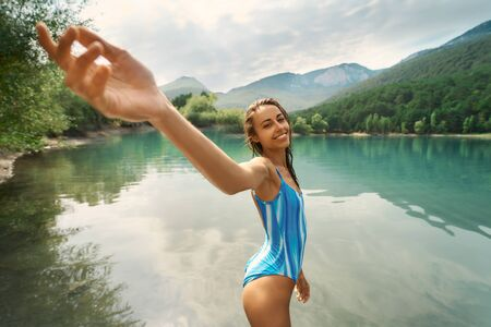 POV and Follow me. Pretty smiling woman standing in mountain lake. Traveler girl enjoying beautiful nature, aqua menthe colored water against mountains. people in nature and travel concept Imagens