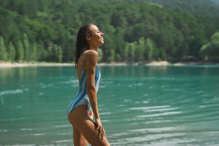 Side view traveler woman in swimsuit posing on background of mountain lake and mountains in the background, aqua menthe colored water. inspiring landscape and beautiful scenery of nature. Imagens