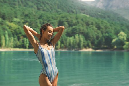 happy adorable woman in blue swimwear standing by mountain lake after swimming. tanned girl hot summer bathing, outdoor adventure, beautiful nature view