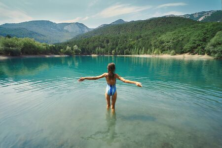 Back view freedom woman in swimsuit standing with open arms in mountain lake and mountains in background. inspiring landscape and beautiful scenery of nature.