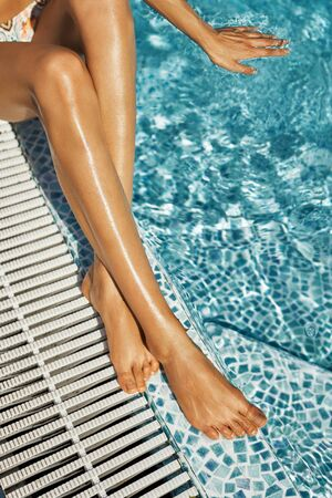 top view legs of woman relaxing, sitting in swimming pool at luxury hotel spa and enjoing clear water. Relaxation and suntanning concept.