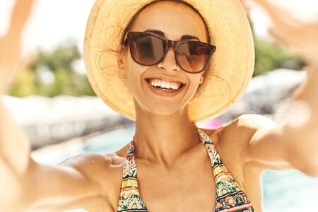 Closeup smiling woman in hat and sunglasses making selfie against summer background. Summer vacation, pool leisure and relaxation Imagens