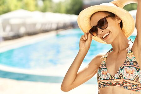 Summer lifestyle portrait of happy carefree woman in hat and sunglasses smiling to camera and standing by swimming pool. Summer vacation, pool lesure concept