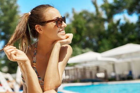 close up portrait of beautiful smiling girl in sunglasses lying at pool edge sunbathing. Pretty happy woman relaxing, enjoying sunny summer day. Imagens