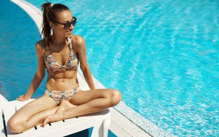 beautiful sexy woman in bikini swimsuit and sunglasses sunbathing near swimming pool. Tanned girl with amazing slim fitness body enjoying sunny summer day. Summer vacation and tanning concept.