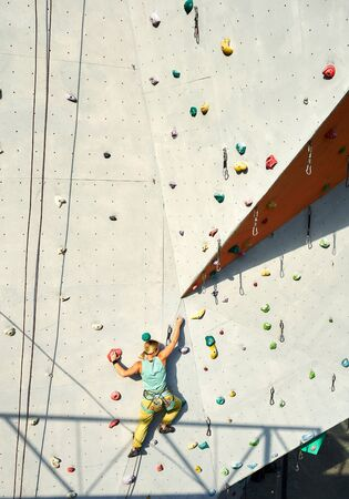 Rear view of sportwoman climber moving up on vertical artificial rock wall. Climbing Gym Wall. extreme sports, strength, training concept