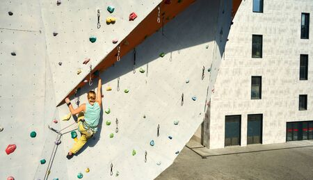 Young woman rock climber climbing on vertical artificial rock wall in outside climbing gym. Sports girl man making hard move on the challenging route. extreme sports, strength, training concept Imagens