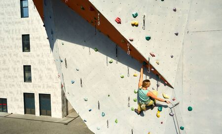 Active sporty woman practicing rock climbing on artificial rock wall in climbing gym. Athletic girl reaching holds, making hard move and gripping hold. Conquering, overcoming and active lifestyle concept.