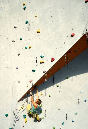 sporty woman practicing rock climbing on artificial rock wall in climbing gym. Athletic girl making hard move and clipping rope. Conquering, overcoming and active lifestyle concept.