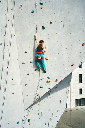 back view young woman rock climber in bright blue pants climbing on vertical artificial rock wall. Climbing Gym Wall. extreme sports, strength, training concept