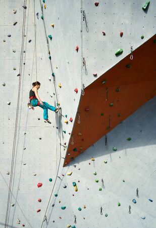 Athletic woman climber in bright blue pants swinging on overhanging artificia rock wall with rope. Climbing Gym Wall. extreme sports, strength, training concept Imagens