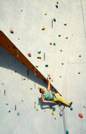 sports woman climber practicing rock climbing on artificial rock wall in climbing gym, resting and chalking hands. extreme sports and active lifestyle concept. Imagens