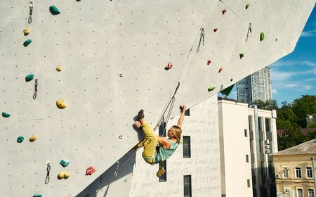 Sports girl climber climbing on artificial rock wall in outside climbing gym. Strong woman making hard move on tough sport route. extreme sports, strength, conquering and active lifestyle concept. Imagens