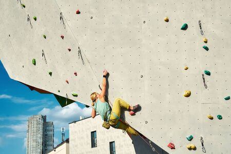 Young woman rock climber climbing on artificial rock wall in outside climbing gym. sports woman working out on extrime sport route. strength, conquering and training concept