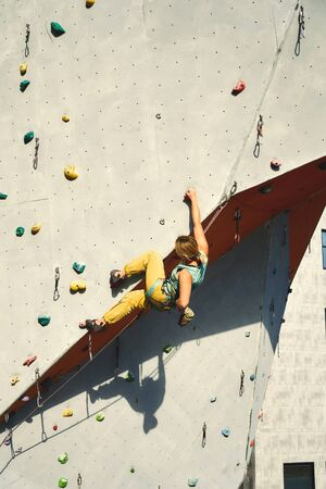 strong woman climber climbing on tough sport route in climbing gym, resting and chalking hands. Climbing Gym Wall. extreme sports, strength, training concept.