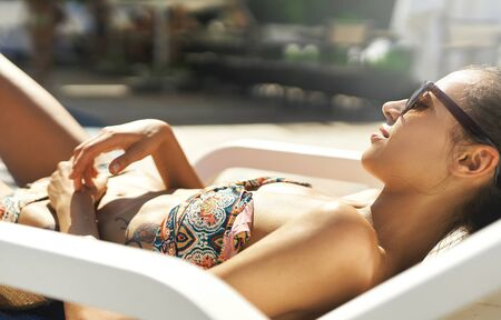 close-up portrait of leisure women in sunglasses sunbathing. Pretty girl relaxing, enjoying hot sunny summer day. Summer vacation and tanning concept. Imagens