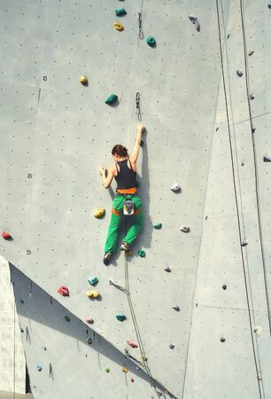 Rear view woman climber in bright green pants climbing on vertical artificial rock wall. Climbing Gym Wall. extreme sports and active lifestyle concept.
