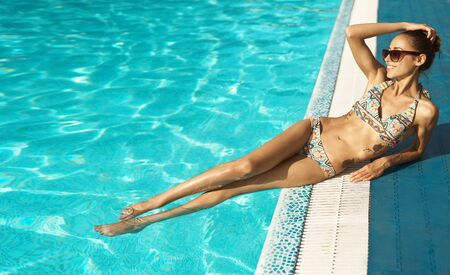 Tanned woman with amazing slim fitness body in bikini and sunglasses enjoying pool leisure and sunbathing. Relaxing, summer holidays and sun tanning concept.