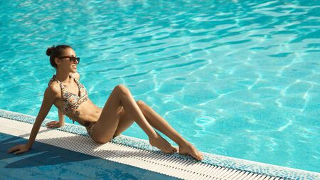 pretty girl with tanned sexy body in bikini and sunglasses posing near swimming pool. beautiful woman relaxing, enjoying pool leisure and sunbathing. Summer lifestyle portrait and suntanning concept.