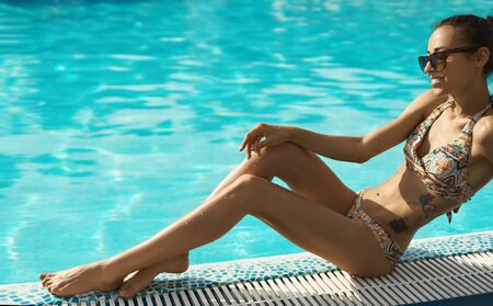 beautiful sexy woman in bikini and sunglasses lying near swimming pool and sunbathing. Tanned girl with amazing slim fitness body enjoying pool leisure and hot sunny summer day. Фото со стока