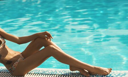 Tanned long woman legs against poll with bright aqua menthe water. Perfect suntan shiny skin. Summer vacation and tanning concept.