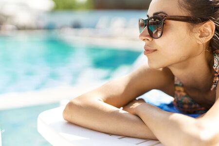 Portrait of leisure women in sunglasses sunbathing near pool. Фото со стока