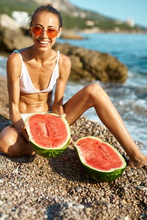 suntanned laughing woman in white bikini and red glasses sitts on pebble beach with two halves of huge ripe watermelon. focus on watermelon Imagens