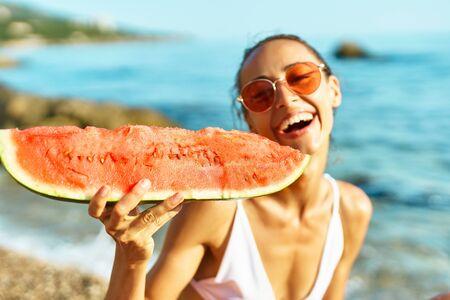 joyful smiling girl in bikini holding huge slice of watermelon sitting on sea beach at seaside at summer vacation travel. focus on watermelon