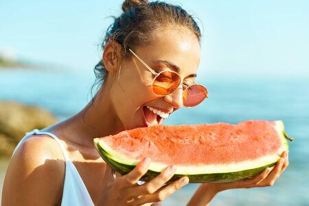 Summer portrait funny girl in red glasses holding huge slice of watermelon and bites him with pleasure. Summer vacation, enjoying juicy fruit