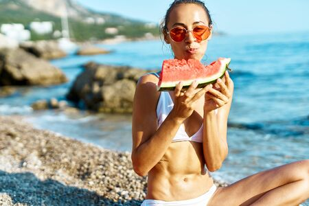 tanned adorable woman in white bikini and red glasses funny eating watermelon on sea beach at summer vacation