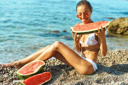 suntanned happy woman with fit body in white bikini holding huge slice of watermelon sitting on sea beach at seashore. Summer vacation, enjoying juicy fruit
