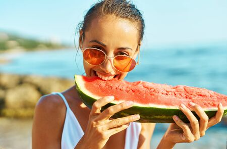 Close-up portrait summer woman in red glasses funny eating watermelon, bites him with pleasure on sea beach at summer vacation, enjoying juicy fruit.
