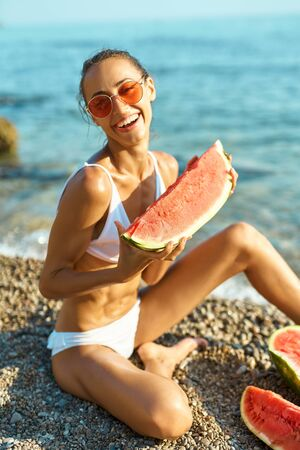 Tanned joyful girl in white bikini and sunglasses holding huge slice of watermelon sitting on sea beach at seaside at summer vacation travel, healthy food nutrition. focus on watermelon Imagens