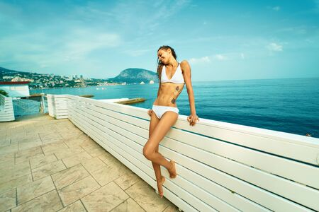 attractive woman tourist with sexy tanned body in white bikini enjoying vacation in Mediterranean. Girl sunbathing on quay with mountain and sea on background. Bright summer vacation portrait Фото со стока