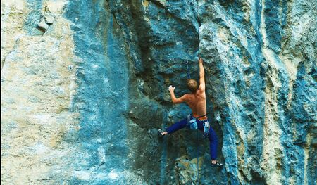 Rear view of strong man rock climber climbing the challenging route on the bright colorful rock cliff, making hard move. Power, strong, concentrated, strength concept Фото со стока
