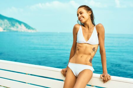 Europe travel vacation. Happy carefree tanned slender model in white bikini against amazing view of sea and mountain. Beach summer luxury travel vacation resort