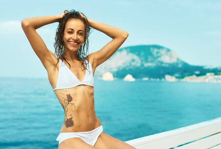 Summer vacation portrait tanned woman in white bikini with wet hair posing by seashore against mountain and blue sky. Happy girl smiling and enjoying travel vacation resort Фото со стока