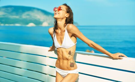 suntanned happy woman with fit body in white bikini and red glasses posing by seashore against mountain and blue sky. Beach summer luxury travel vacation resort Imagens - 150192129