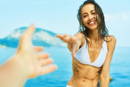 first person view of happy suntanned woman in bikini against i against amazing view of sea and mountain. Travel girl giving someone her hand. follow me, POV