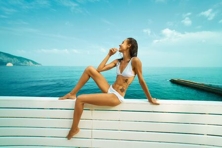 Tanned woman in white bikini with wet hair sits on white fence by seashore against blue sky. smiling girl enjoying amazing sea view