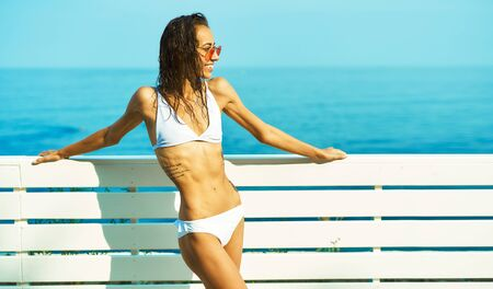 Tanned bikini girl with sexy fit body sunbathing and posing by seashore. Woman with wet hair in red glasses enjoying travel holidays at resort Фото со стока