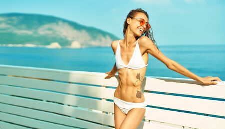 summer portrait happy woman with sexy fit body in white bikini and red glasses posing by seashore against mountain and blue sky. Beach summer luxury travel vacation resort