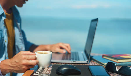 man freelancer working on laptop computer, keyboarding text and holding cup with coffee on beach. Technology and travel. Working outdoors. Freelance concept.