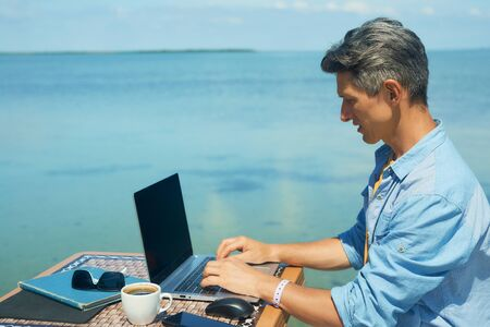 business man working the beach at morning by the sea, using laptop. Freedom, remote work, freelancer, technology, internet, travel and vacation concepts