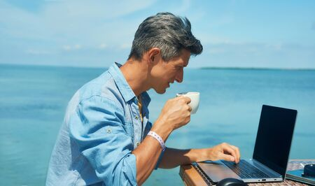 man freelancer working at morning on the beach by the sea, drinking coffee, using laptop computer. dream office job workplace. Freelance concept