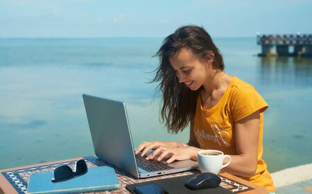 female freelancer working by the sea, using laptop computer. Freelance work concept, technology, travel and vacation