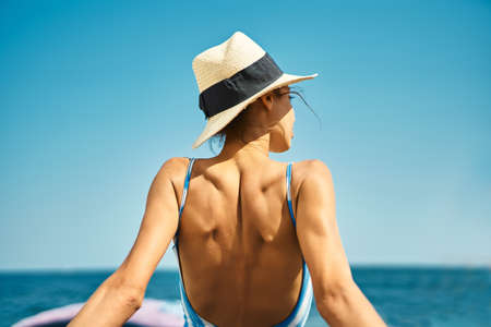 Rear view woman on the beach. Happy freedom girl in straw hat and swimsuit enjoying summer beach vacation in hot sunny day Imagens - 150796190