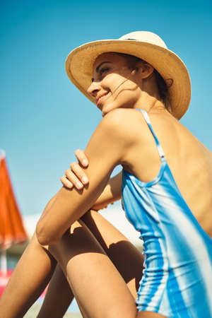 Happy woman in straw hat and swimsuit enjoying beach at ot summer sunny day. smiling girl relaxing and sunbathing in traveling vacation Imagens - 150795799